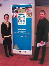 Foto: Ein Schulungsteam (eine Frau und ein Mann) steht vor einer Informationswand